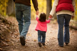 Girl walking in woods, holding parents hands