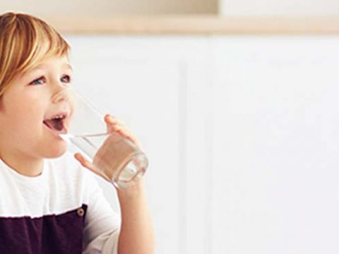 Child drinking a glass of water