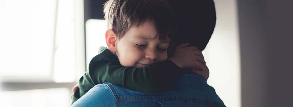Child cudding his father